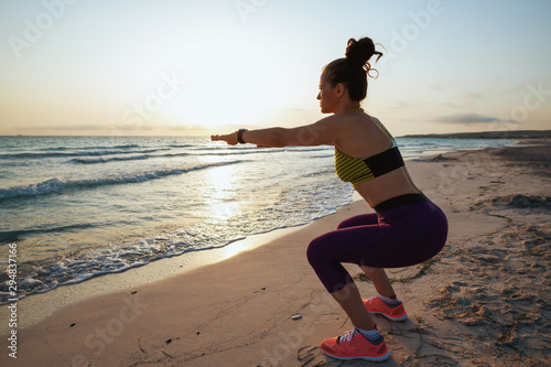 healthy woman on seashore in evening doing squats Fototapeta
