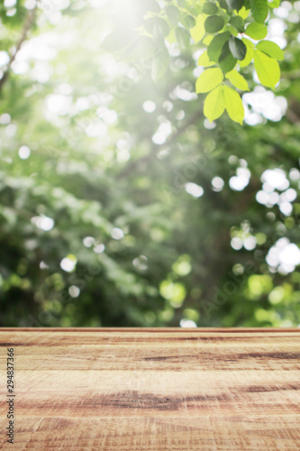 Pinturas sobre lienzo  Wooden table and blurred green leaves nature bokeh background.