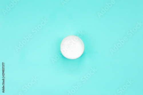Fotomural  Cosmetic cream or body cream container on blue background