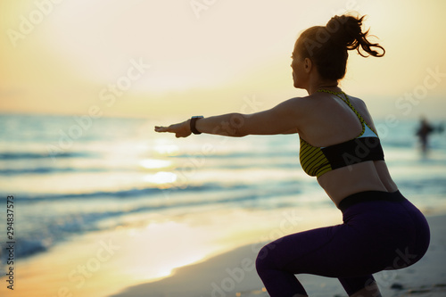 healthy woman on seashore at sunset doing squats Wallpaper Mural