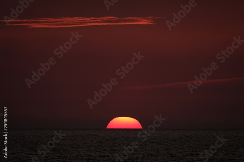Photo sur Aluminium Marron Beautiful shot of the sun going down in a red sky