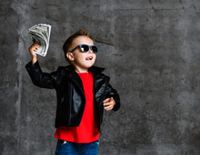 Looking Up Rich Kid Boy In Sunglasses, Leather Jacket And Red T-shirt Holding A Bundle Of Dollars Going To Throw It Up