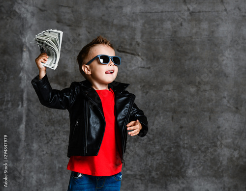 Fototapeta Looking up rich kid boy in sunglasses, leather jacket and red t-shirt holding a bundle of dollars going to throw it up obraz