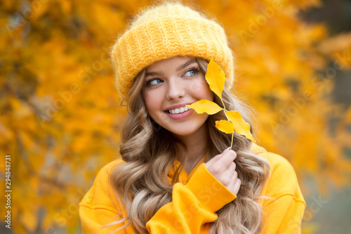 Fototapeta Beautiful girl walking outdoors in autumn. Smiling girl collects yellow leaves in autumn. Young woman enjoying autumn weather. obraz