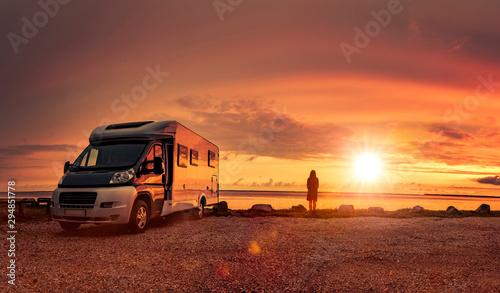 Glückliches Paar mit Wohnmobil am Strand Fotobehang