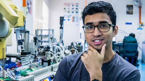 Fotomural  A young Malay engineering student with spectacles working in the lab and thinking by holding chin