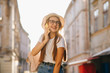 Young woman speak by her phone , smart casual outfit, hat and clear glasses, positive emotions. Woman using her mobile phone in sunny autumn day. Lifestyle