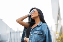 Cute Young Hipster Woman In Fashionable Sunglasses In A Trendy Black T-shirt In A Stylish Denim Jacket Straightens Hair. Pretty Attractive Girl Brunette Resting In The City In An Autumn Bright Day.