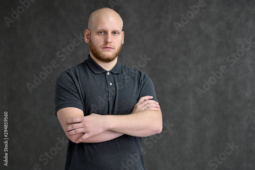 Fototapeta Portrait of a handsome bald man in a gray t-shirt on a gray background in the studio