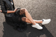 Glamorous Young Woman In White Stylish Sneakers In A Vintage Leather Jacket In An Elegant Skirt With A Mobile Phone Sits On The Asphalt On A Sunny Day.Collection Of Women's Autumn Clothing. Close-up.