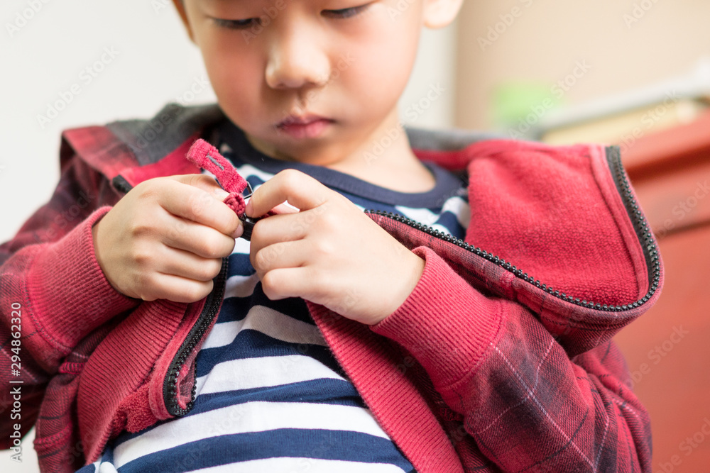 Fototapeta Child Development concept: Close up of a little preschool boy learning to get dressed, zipping his striped red hoodie. Montessori practical life skills - Care of self, Early education from daily life.