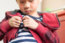 Child Development Concept: Close Up Of A Little Preschool Boy Learning To Get Dressed, Zipping His Striped Red Hoodie. Montessori Practical Life Skills - Care Of Self, Early Education From Daily Life.