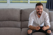 Portrait Young Handsome Man Playing Video Game To Win, Holdong Joystick On Sofa At Home