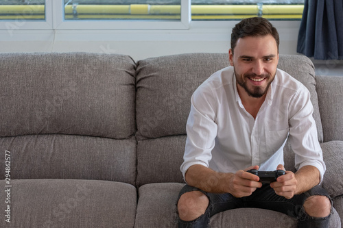 Fotomural Portrait young handsome man playing video game to win, Holdong joystick on sofa