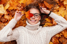 Funny Young Hipster Woman In A Fashionable Knitted Sweater In Stylish Glasses With An Orange Leaf In Hands Expresses Surprise While Lying On Autumn Foliage In The Forest. Positive Girl Model Resting.