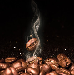 Fototapeta Popularne Roasted coffee beans. Seeds of freshly roasted coffee with smoke. Coffee beans closeup with emphasis on the grain with smoke.