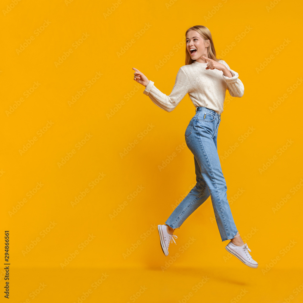 Fototapety, obrazy: Young girl jumping in air and pointing on copy space
