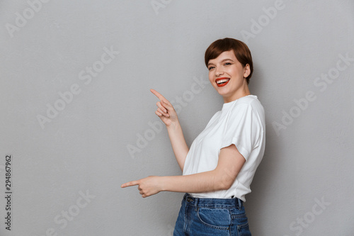 Foto  Image of lovely brunette woman pointing fingers aside at copyspace