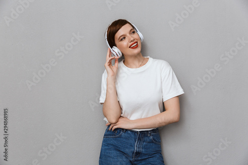 Leinwand Poster  Image of cute woman smiling while listening to music with headphones