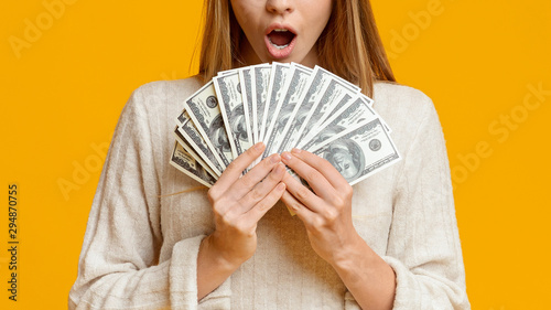 Fotografía Amazed young woman holding bunch of money banknotes, celebrating profit