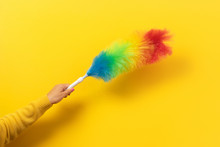 Colorful Feather Duster In Hand On Yellow Background. Cleaning Concept.
