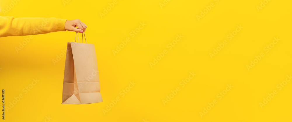Fototapety, obrazy: Woman hand holding paper shopping bag on yellow background. Discounts and sale of concept. Panoramic image