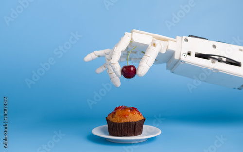 Montage in der Fensternische Kirschblüte Robot hand putting fresh cherry on top of the cupcake