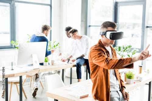 young businessman using vr headset and touching something with finger while multicultural colleagues working in office - 294874194