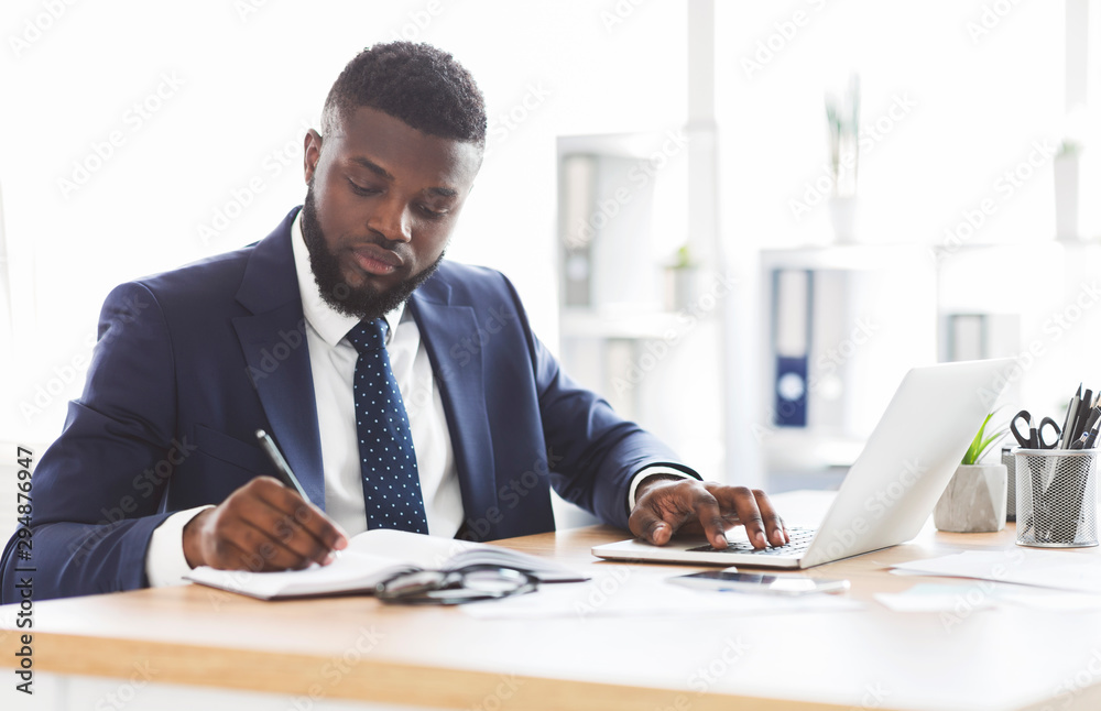 Fototapeta Successful black businessman working hard in office