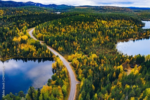 Route dans la forêt Aerial view of road and colorful autumn forest with mountains and blue lakes in Finland.