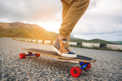 Close-up of male legs in rag sneakers on a longboard on the background of asphalt at sunset. Big skateboard with man legs. Youth leisure concept