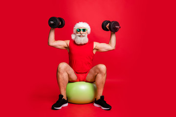 Full size photo of cheerful santa claus in eyeglasses eyewear having nicholas hat cap sit on fit ball practice two dumbbells wear sportswear isolated over red background