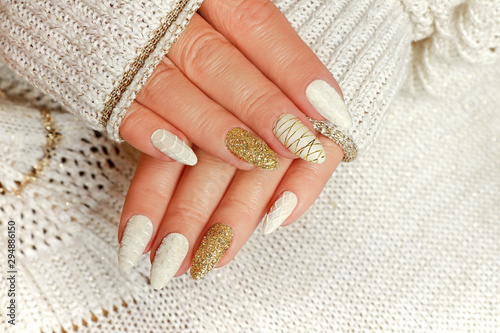Fotografia Knitted sand manicure on long oval nails with golden sequins and threads on the female red in a jacket