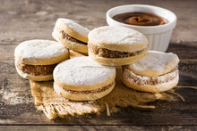 Traditional Argentinian Alfajores With Dulce De Leche And Sugar On Wooden Table