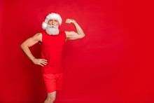 Portrait Of Serious Santa Claus In Hat Showing His Triceps In Training Wearing Sportswear Cap Isolated Over Red Background