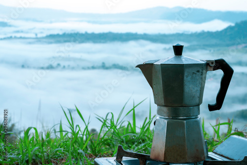 Fototapeta Moka coffee pot on a green grass with dew drops The background is a foggy mountain