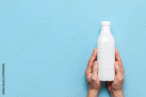 White plastic bottle containers for dairy products in male hands on blue background top view flat lay. Plastic Kefir Yogurt Milk Bottle. Packaging template mockup. Layout for your design