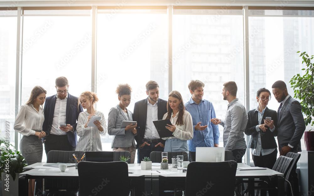 Fototapeta Diverse business team discussing work during break