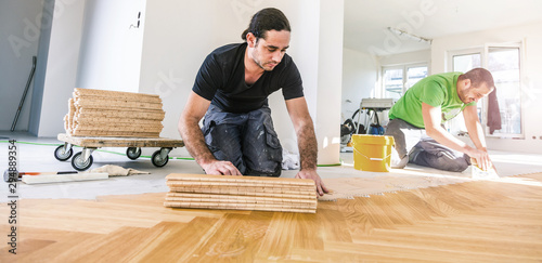 Obraz Carpenter on work putting wood parquet pieces. Home construction  - fototapety do salonu