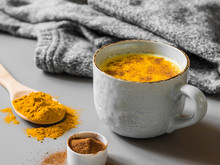 Turmeric Latte With Milk And Cinnamon. Elixir Of Health And Vivacity. Traditional Healthy Indian Detox Drink. Grey Background