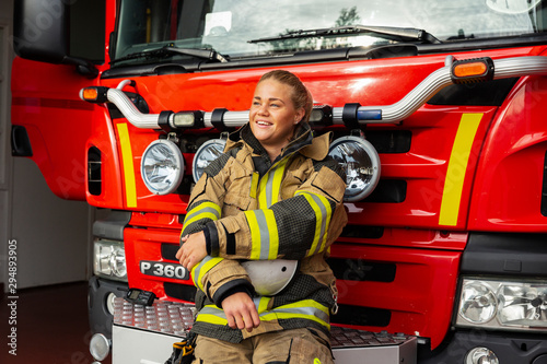 Female firefighter leaning on fire engine