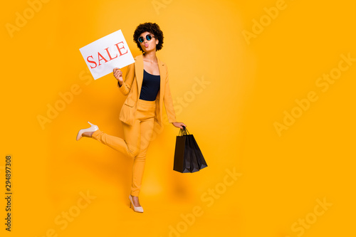 Full length photo of romantic afro american girl have autumn leisure time hold bags recommend bargain send air kisses wear beauty style jacket trousers high-heels isolated yellow color background