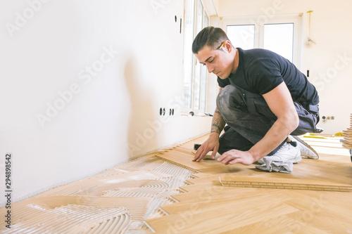 Obraz Handwerker bei der arbeit, fischgrät parkett verlegen ,sockelleisten montage . - fototapety do salonu