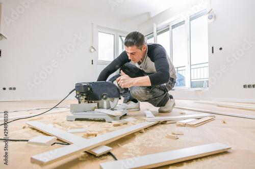 Handwerker bei der arbeit, fischgrät parkett verlegen ,sockelleisten montage Wallpaper Mural