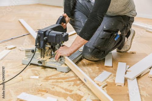фотография Handwerker bei der arbeit, fischgrät parkett verlegen ,sockelleisten montage