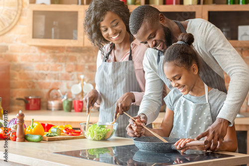 Fototapeta Afro parents teaching their daughter how to cook obraz