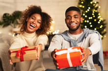 Black Couple Holding Christmas Gift Boxes And Smiling