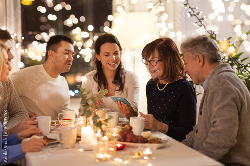 Fototapety, obrazy: celebration, holidays and people concept - happy family with smartphone having tea party at home