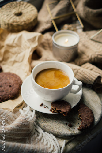 Obraz Cup of coffe with milk and chocolate cookies on warm wool blanket - fototapety do salonu