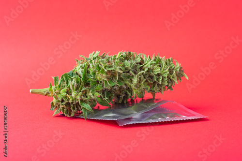 Canvas marijuana and condoms on red background,contraception for intercourse with canna
